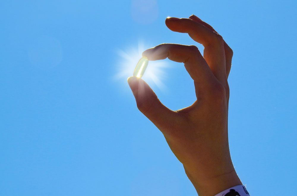 A person's hand holding a capsule directly infront of the sunlight
