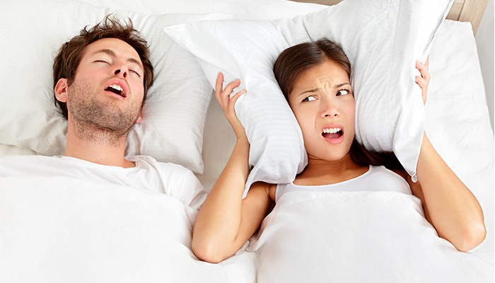 Woman trying to block out the sound of partner snoring