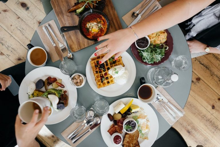 Table of breakfast food with womans hand reaching for more food