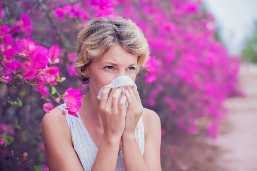Woman with allergy symptom and blowing her nose