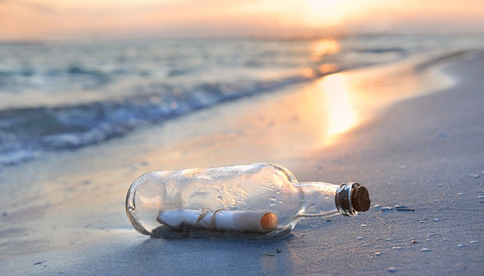 A message in a bottle on a a beach at sunset