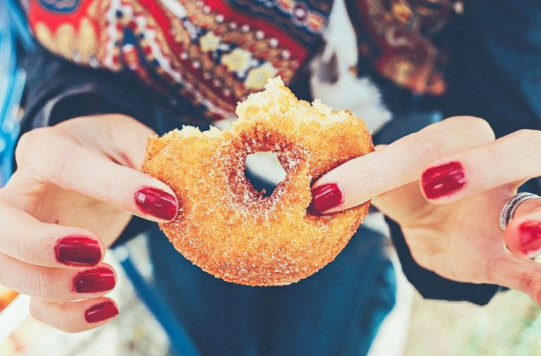 Woman holding a sugary donut