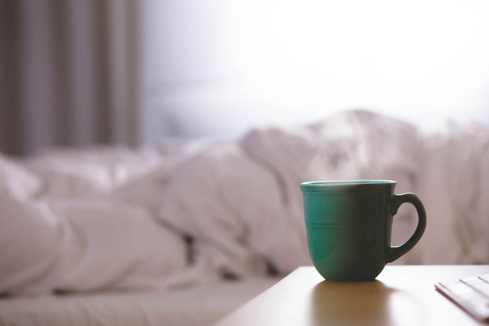 Teal mug on the edge of a nightstand with a bed in the background