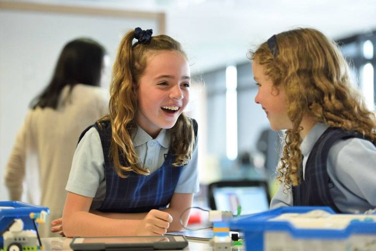 Two young girls in uniform in a school environment