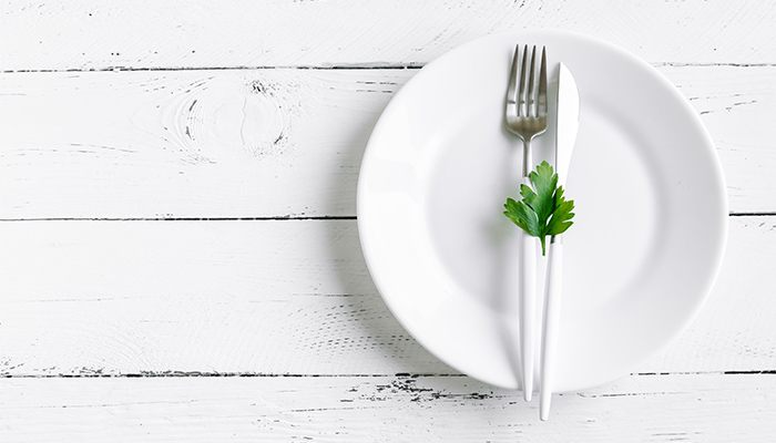 Top down image of a clean plate with a fork and knife.