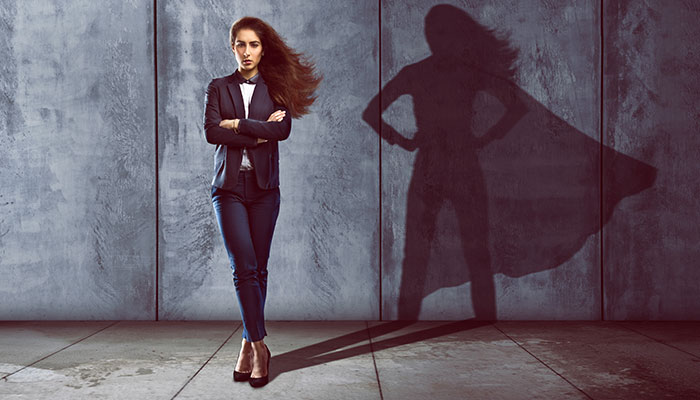 Woman standing in powerful stance as her shadow looks like a super hero