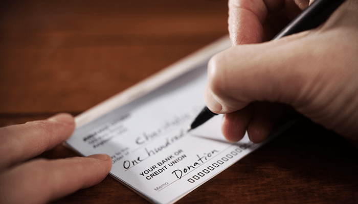 Close-up of person writing a donation check.