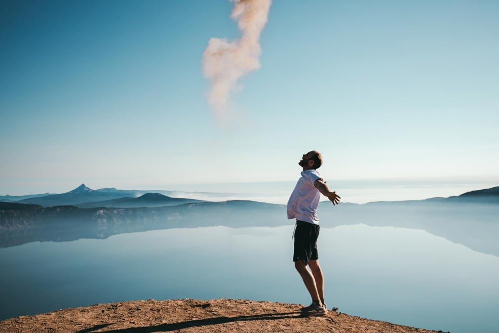 Man standing on the edge of a calm lake with mountains in the distance while yelling with his arms open