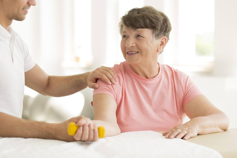 Image of an elderly woman lifting a light-weight dumbell with a trainer helping her form
