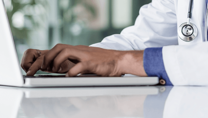Close-up of doctors hands typing on a computer.