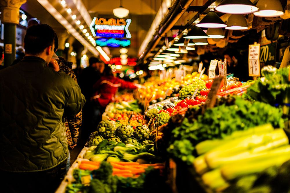 Image of fruits and vegetable stand in a grocery store, with a walkway of customers next to it looking at produce