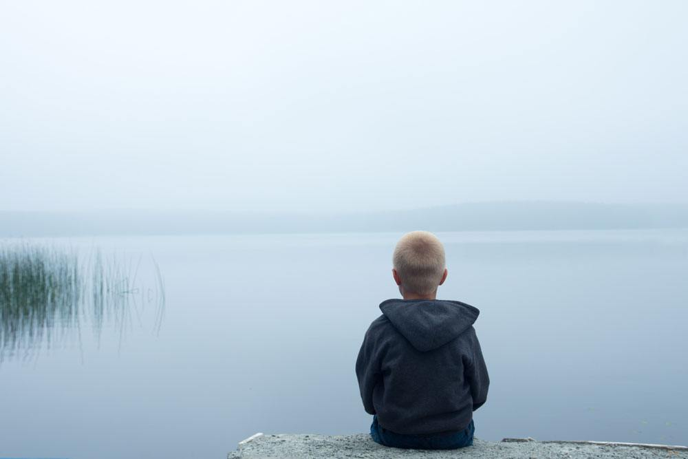 A boy sitting on the edge of a lake looking out over the foggy water